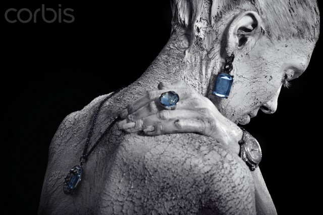Studio shot of woman covered in mud wearing jewelry